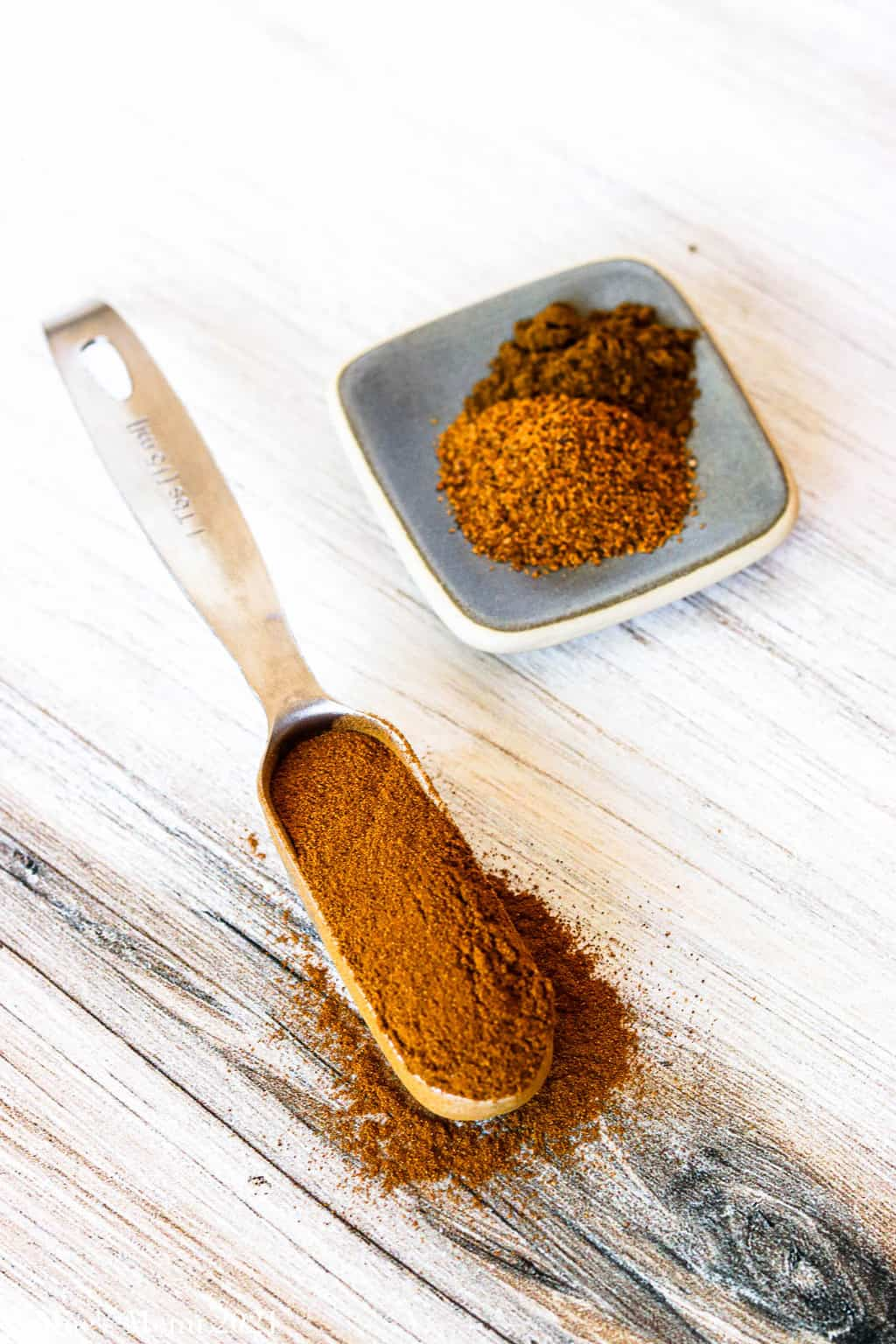 An up-close shot of a tablespoon of cinnamon in front of a small dish of nutmeg and cloves