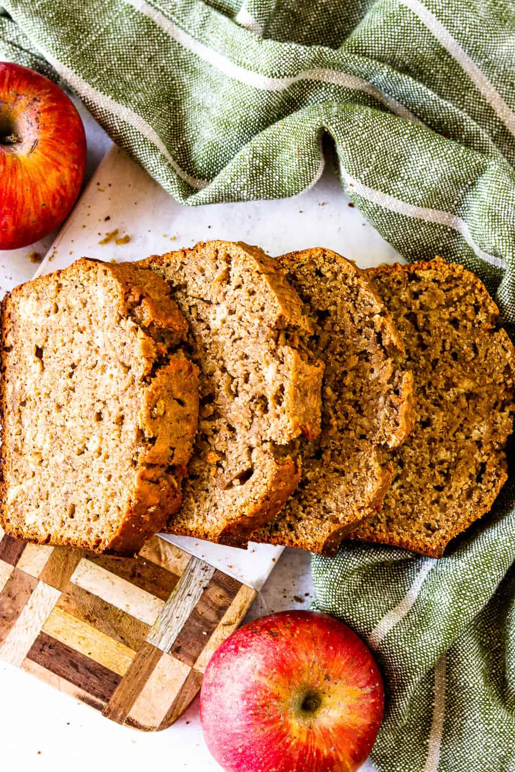 A cutting board with slices of healthy cinnamon apple bread resting on top