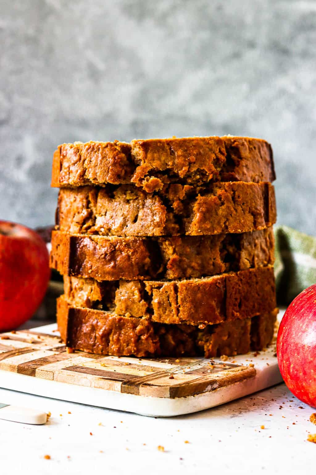 Thick slices of cinnamon apple bread sacked on each other on a cutting board