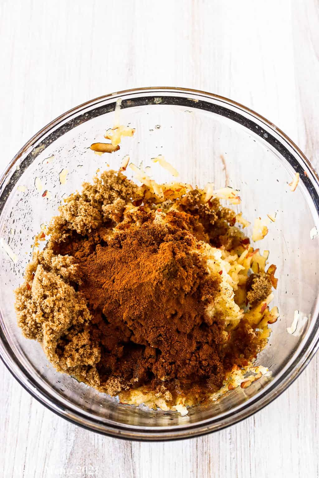 A mixing bowl with shredded apples, cinnamon, nutmeg, and cloves