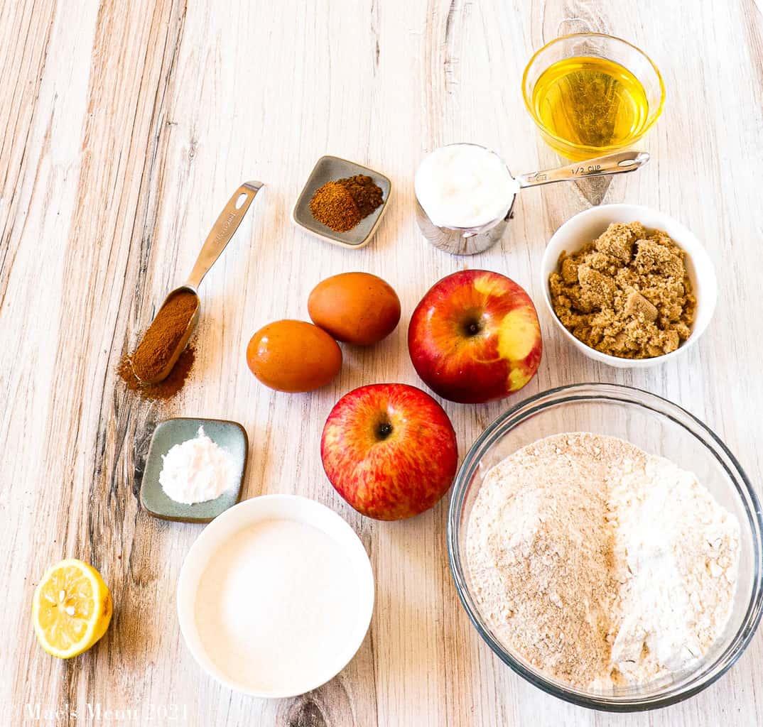 All the ingredients for healthy cinnamon apple bread: apples, eggs, avocado oil, brown sugar, flour, sugar, baking soda, lemons, cinnamon, nutmeg, and cloves
