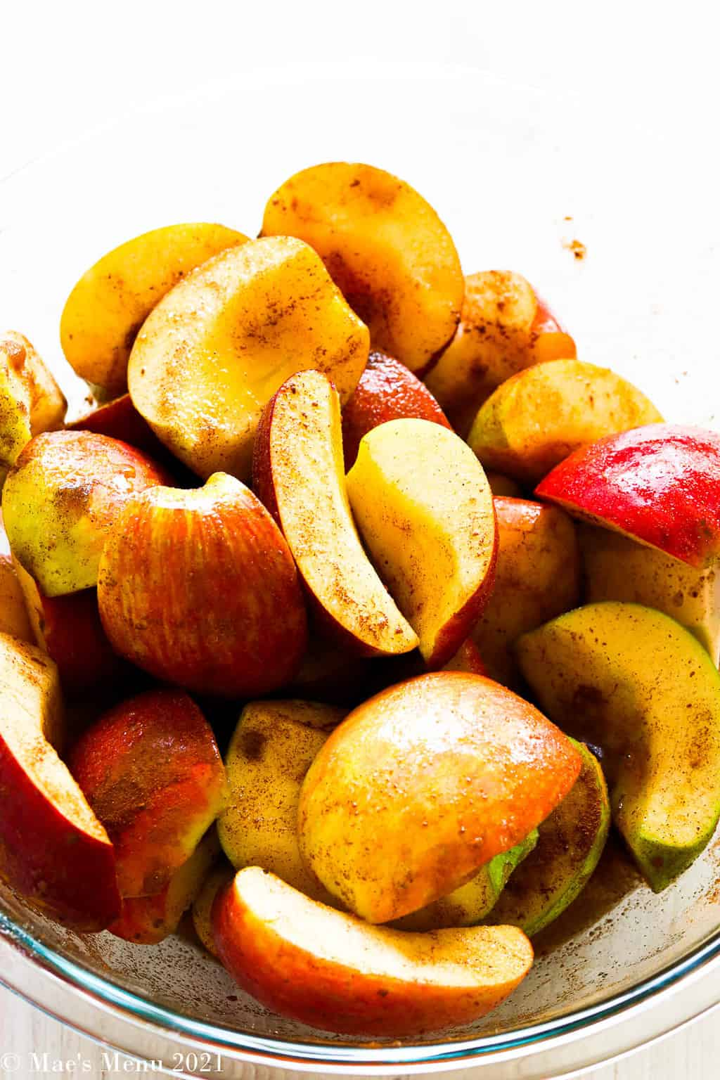 A side shot of apples covered in sugar and spices in a large mixing bowl