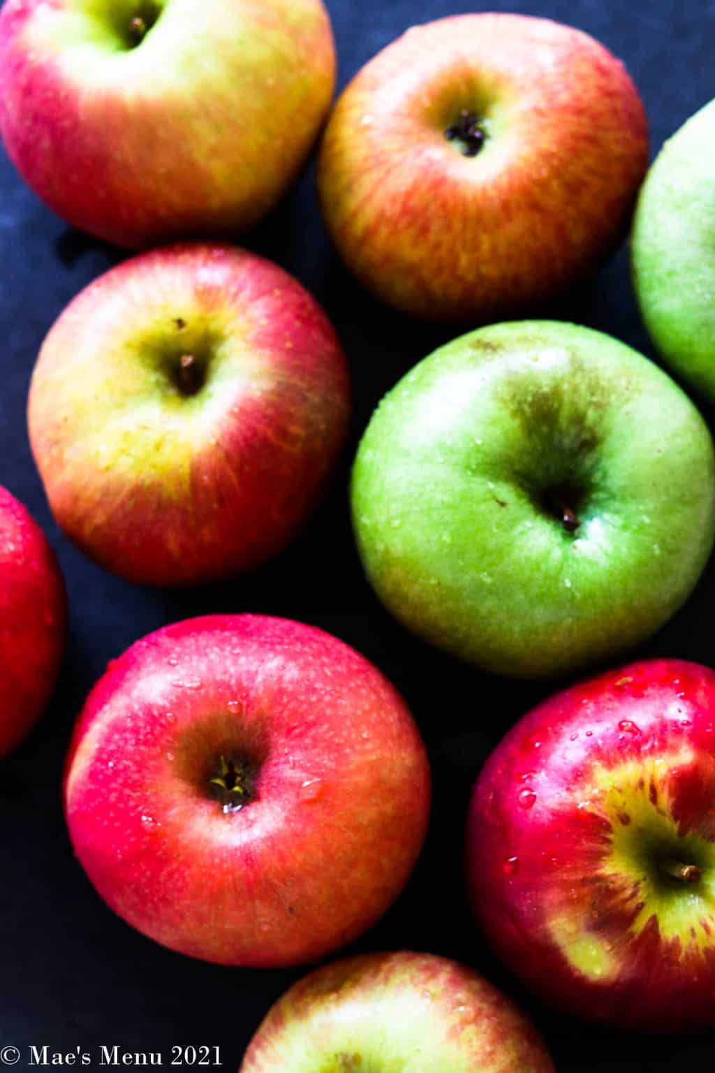 An up-close overhead shot of apples on a black background