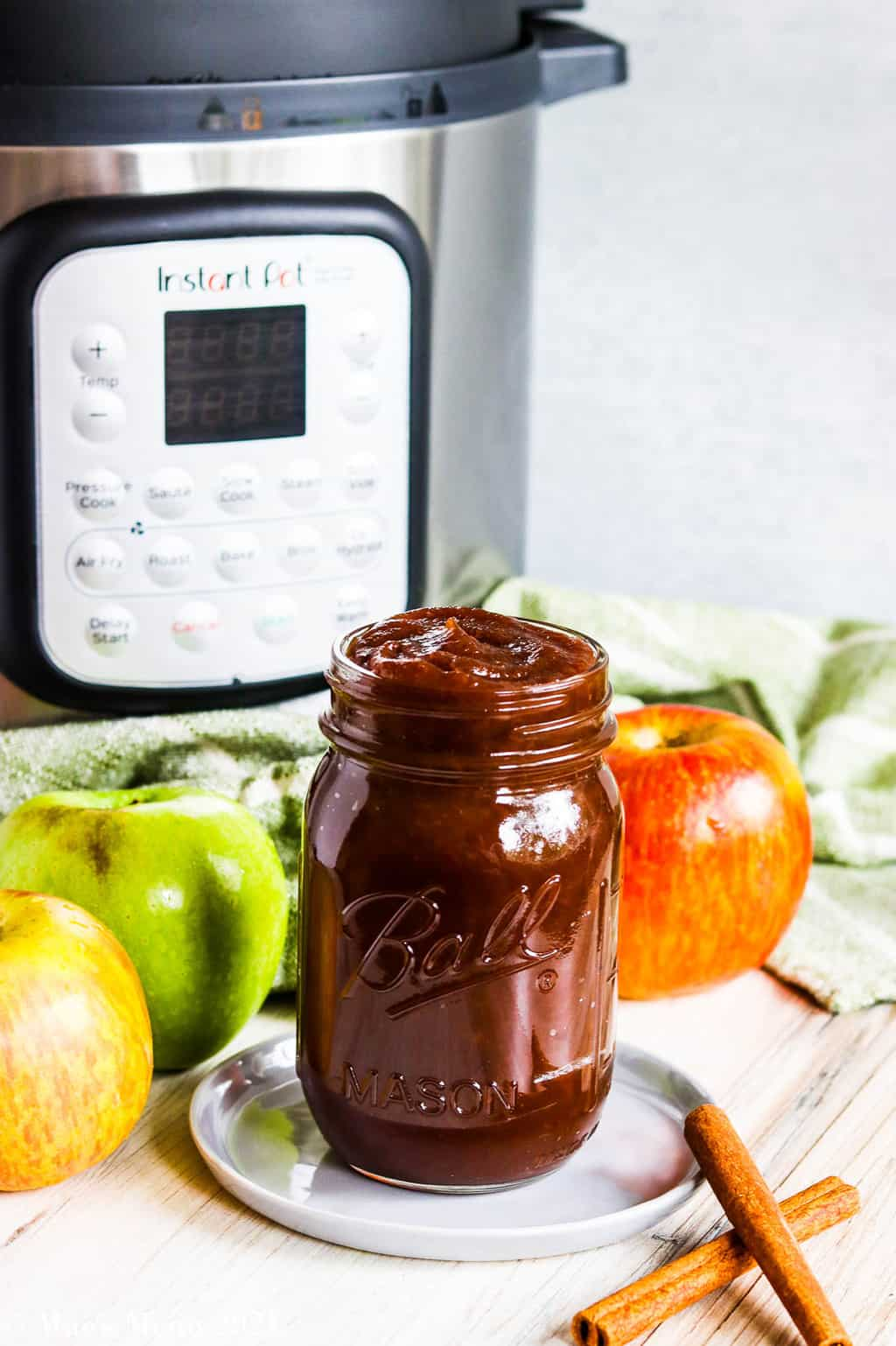 A ball jar of apple butter in a glass jar in front of an instant pot with apples and cinnamon
