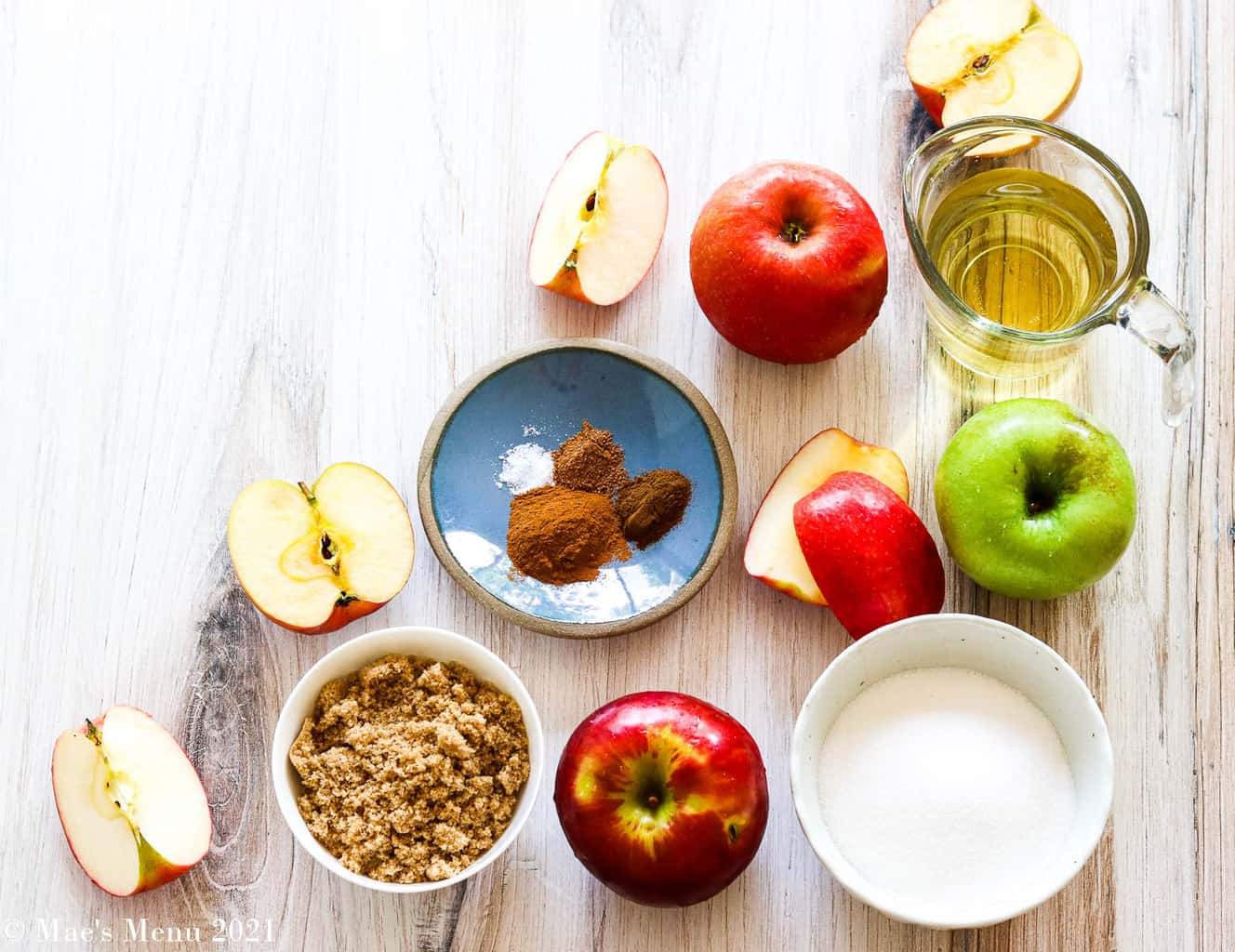 All the ingredients for instant pot apple butter: apples, sugar, brown sugar, cinnamon, nutmeg, cloves, and apple juice
