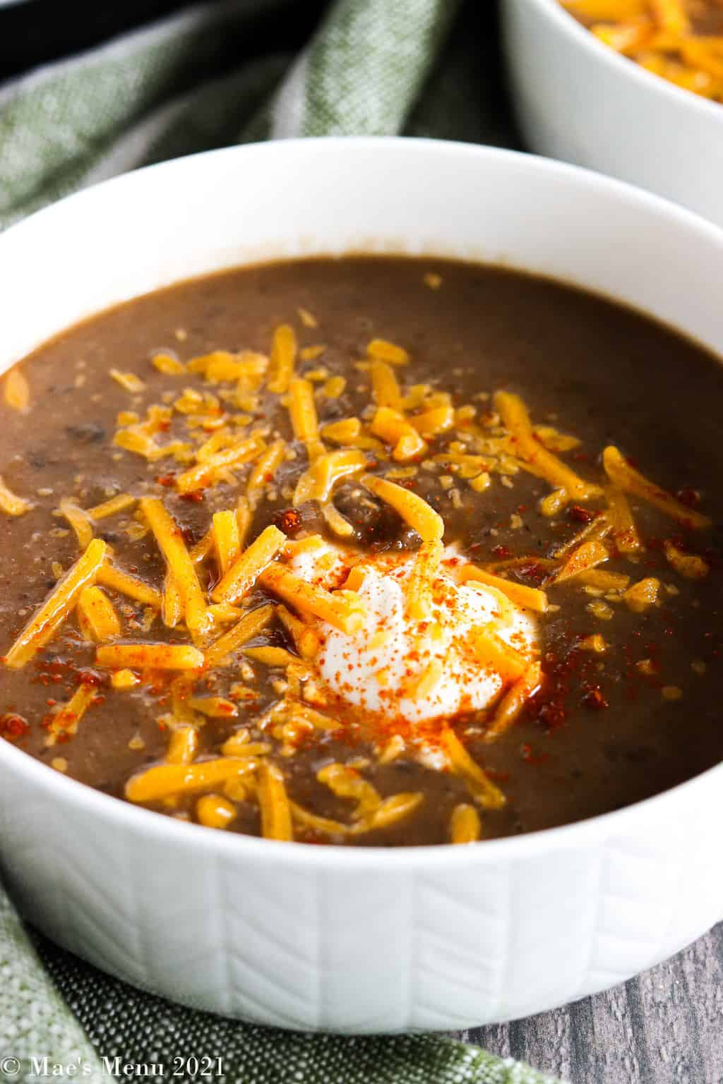 A side shot of a bowl of instant pot bean soup with shredded cheese, sour cream, and seasonings