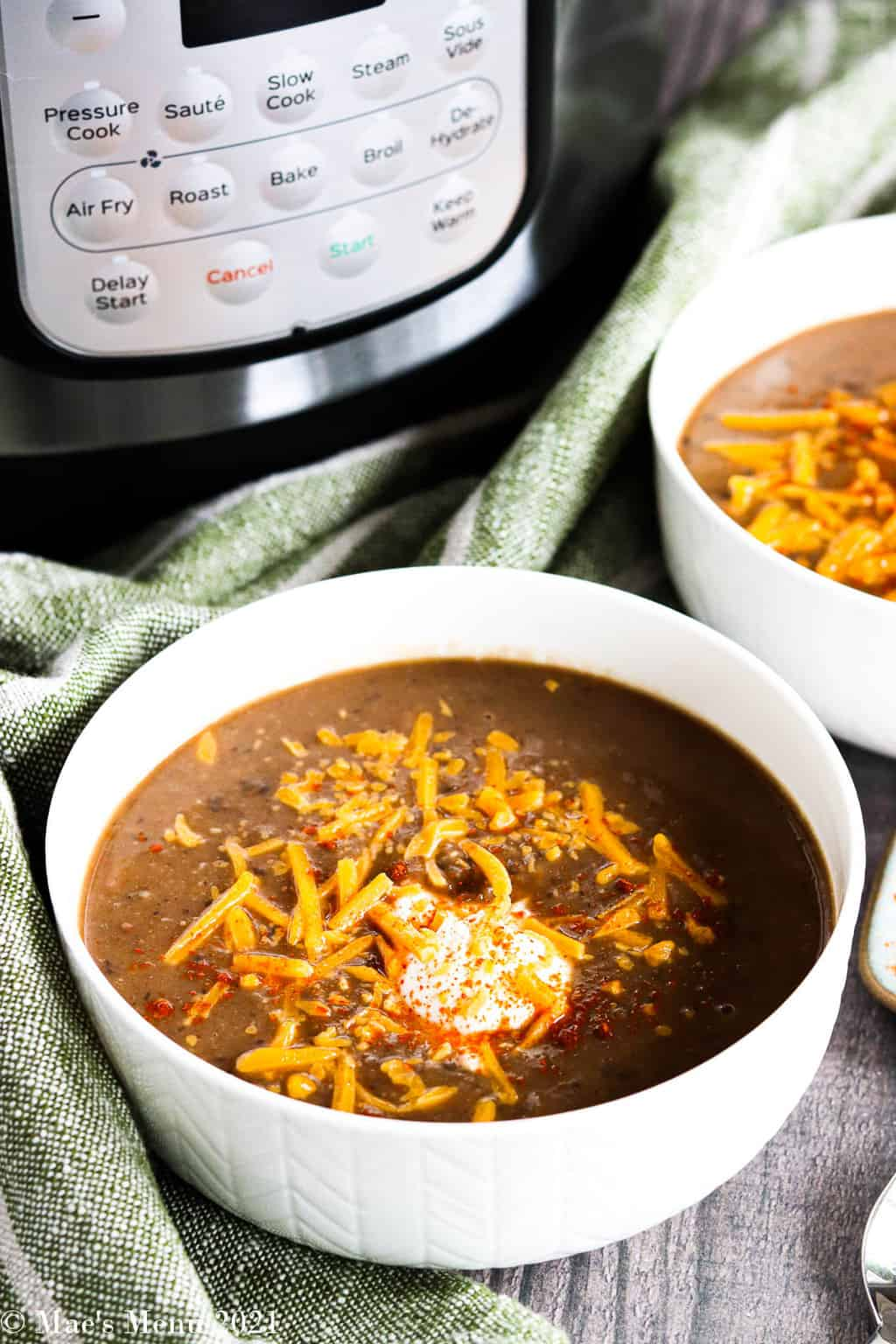 Two bowls of Instant Pot bean soup in front of a pressure cooker