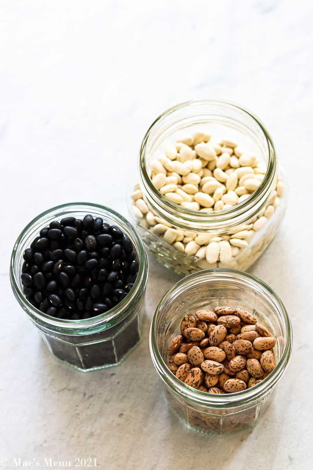 3 small glass containers of dried beans: white beans, black beans, and pinto beans