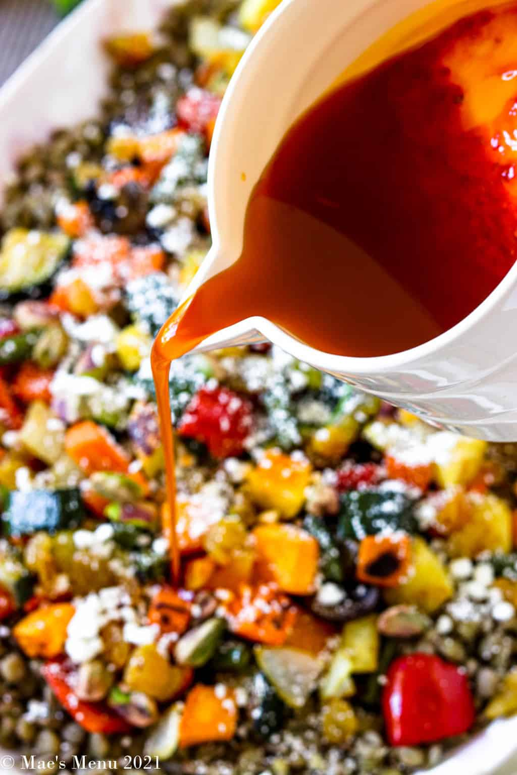 Drizzling harissa salad dressing over the Moroccan roasted vegetable salad dressing