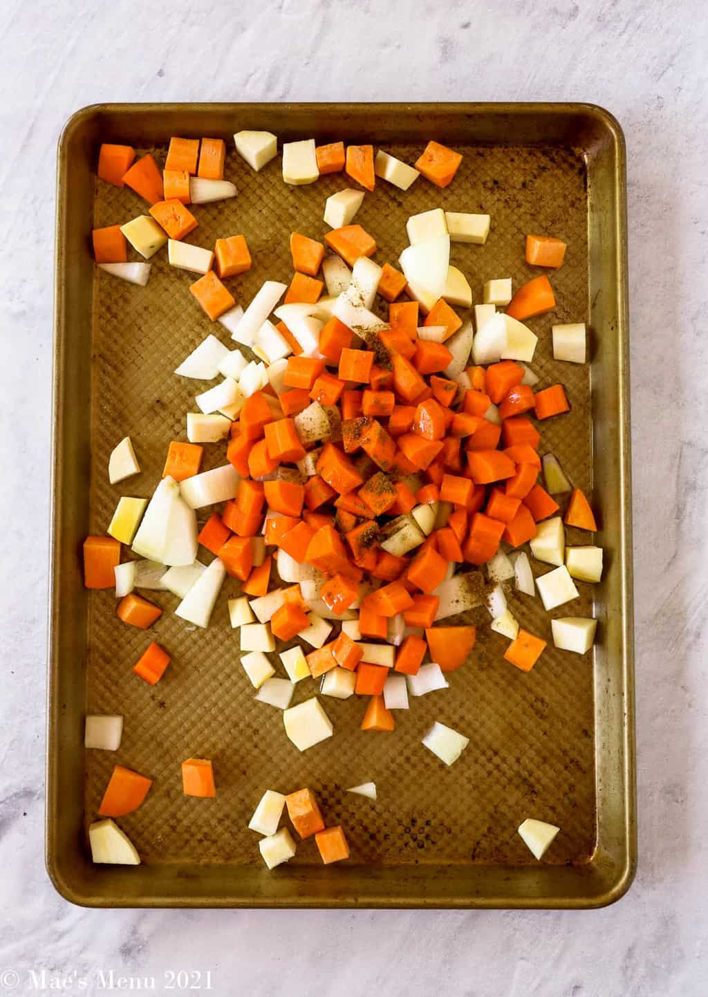 An overhead shot of a roasting pan with carrots, sweet, potato, and onions