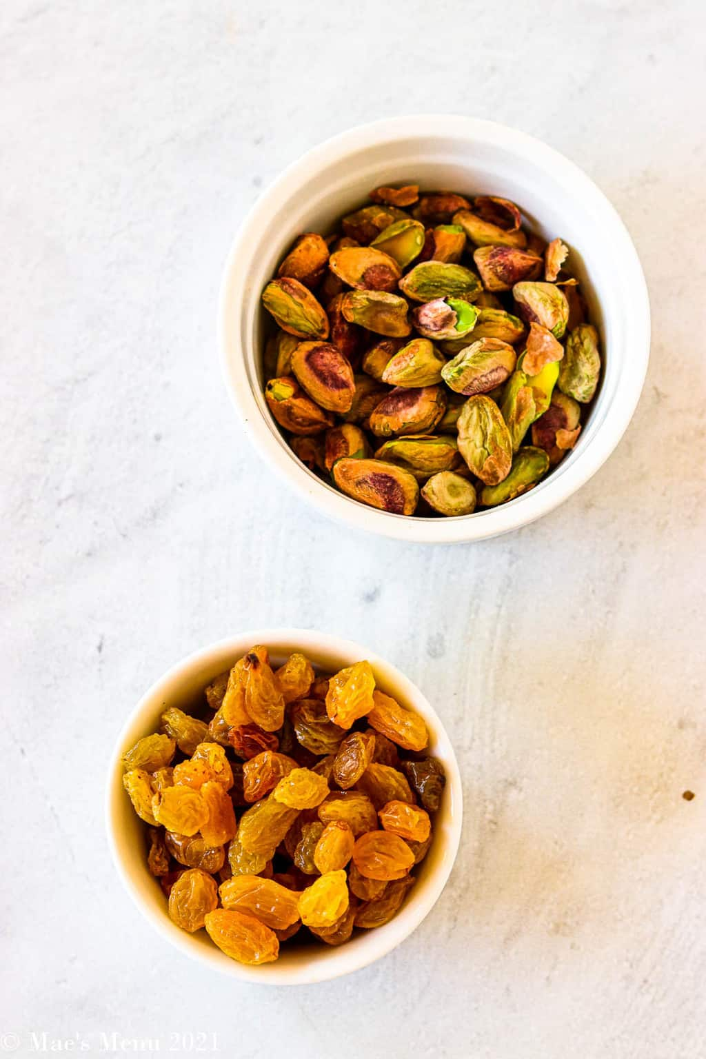 A small dish of golden raisins and a small cup of shelled pistachios