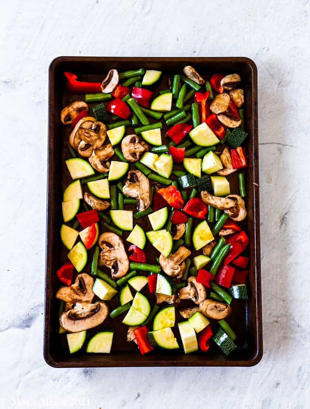 A roasting pan of zucchini, red pepper, mushrooms, and green pepper
