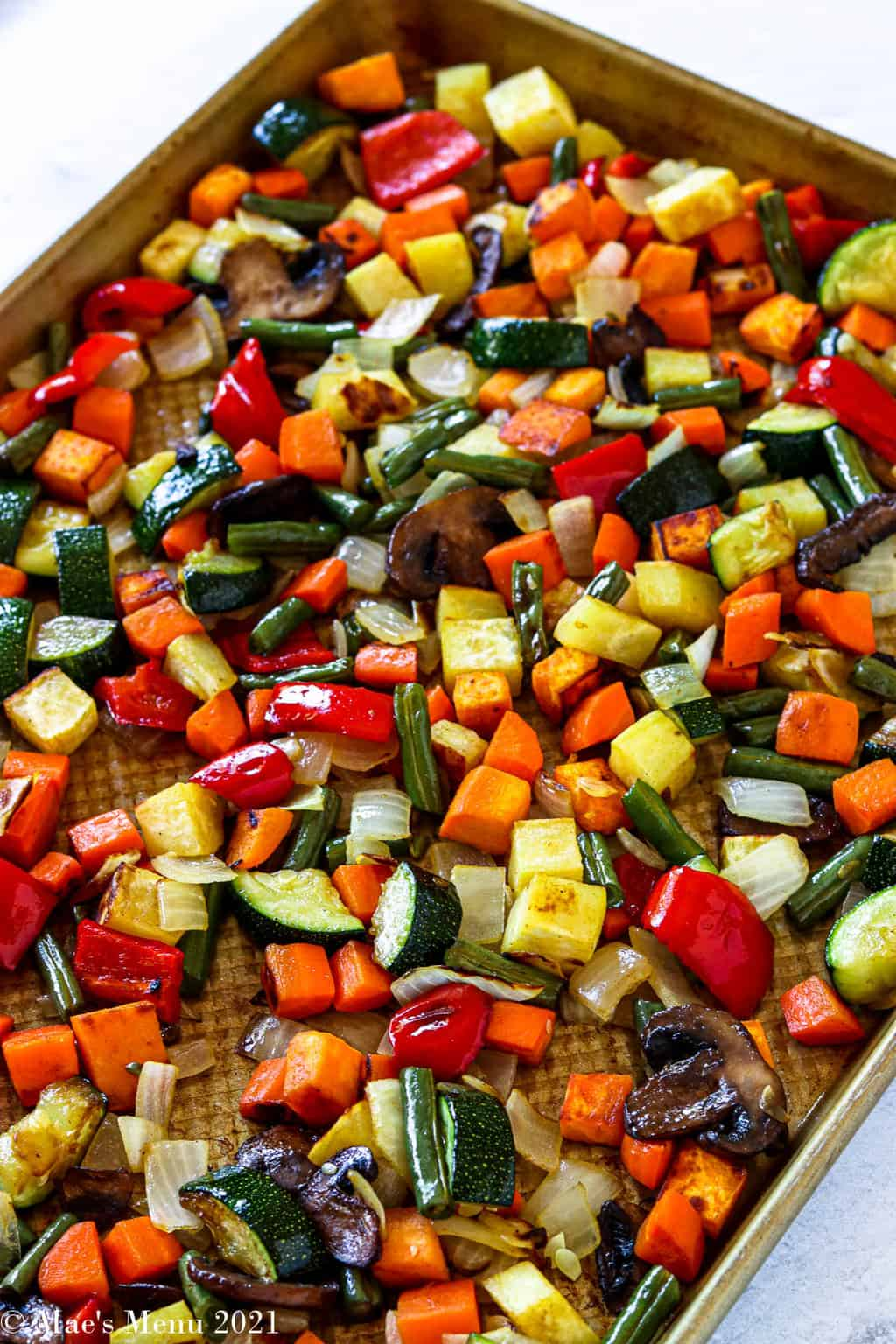 A side shot of a roasting pan of roasted veggies