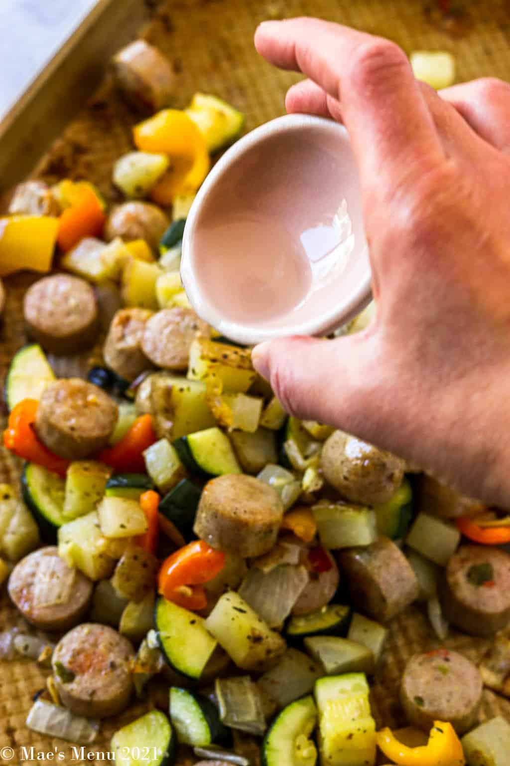 Pouring white balsamic vinegar over a roasting pan of veggies and sausage