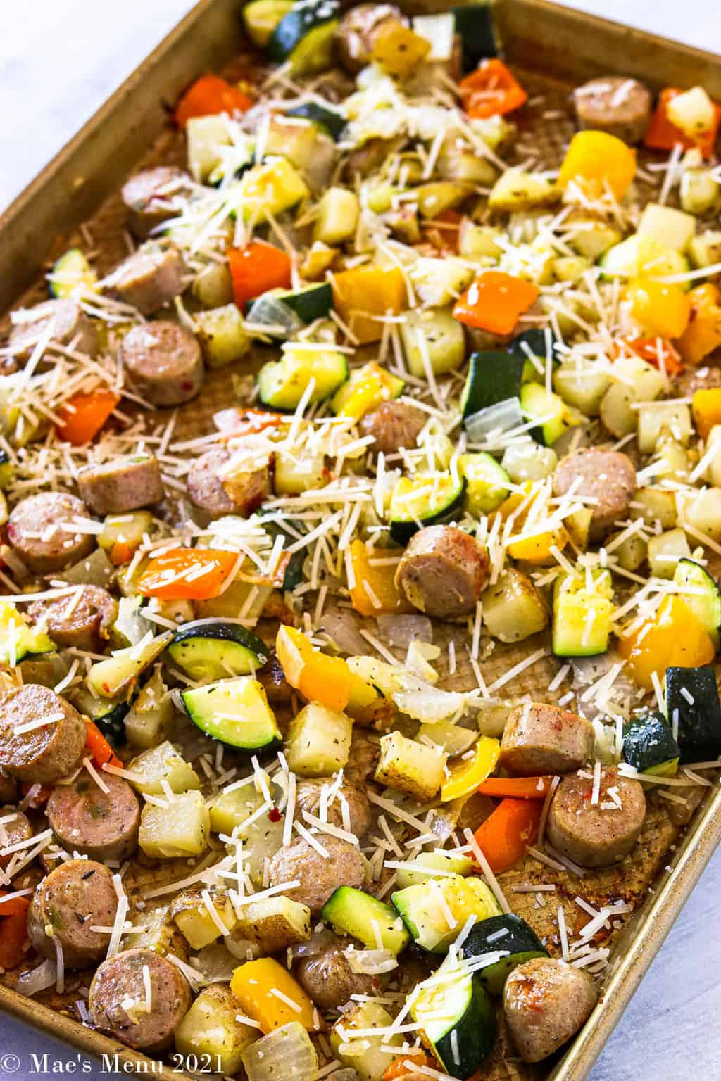A side shot of a roasting pan with veggies, potatoes, sausage, and shredded parmesan cheese