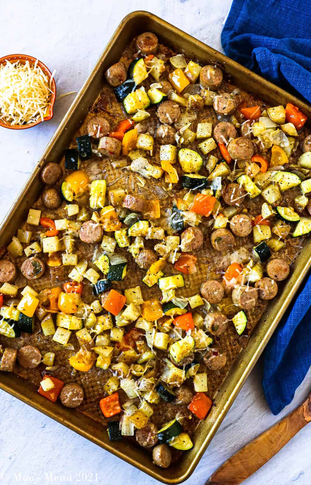 An overhead shot of a sheet pan with roasted sausage and veggies and melted parmesan cheese