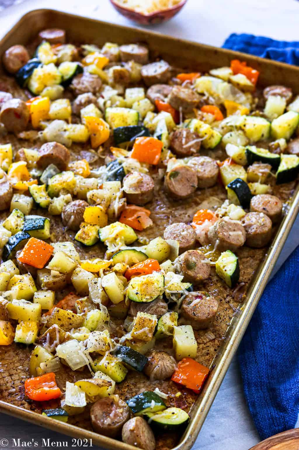 A side angled shot of a tray of sheet pan sausage and veggie