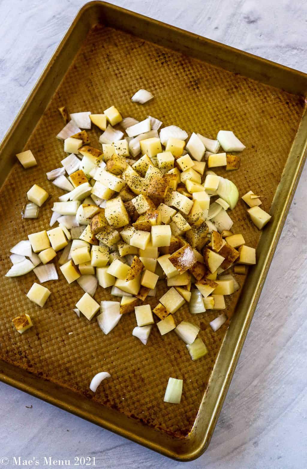 A baking pan with potatoes, onions, and seasoning