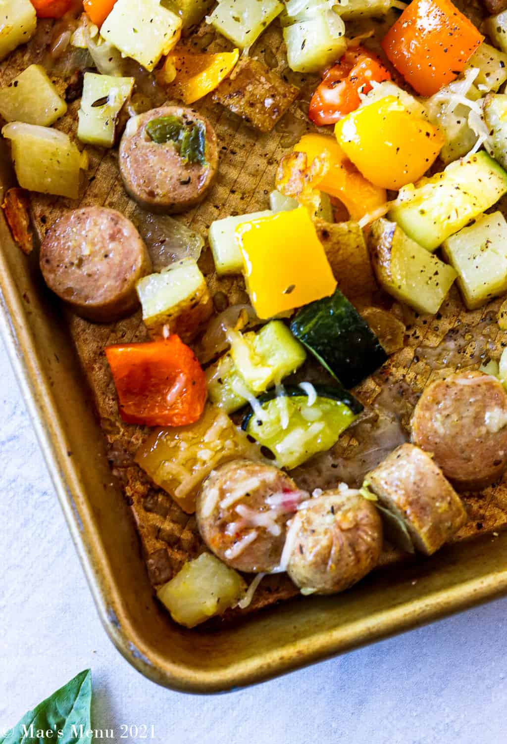 An up close overhead shot of a corner of sheet pan sausage and veggies