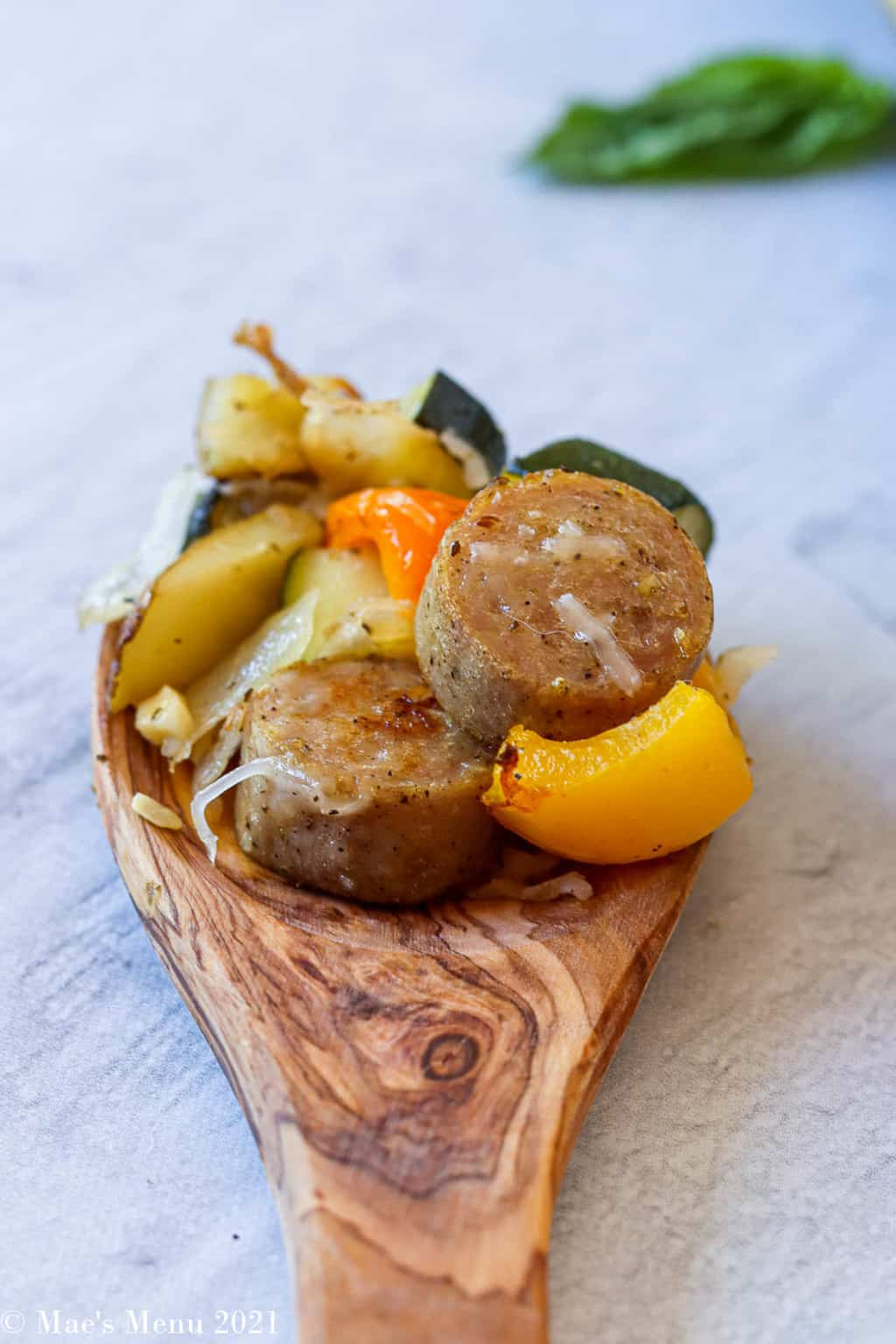 A side shot of a spoonful of sheet pan sausage and veggies