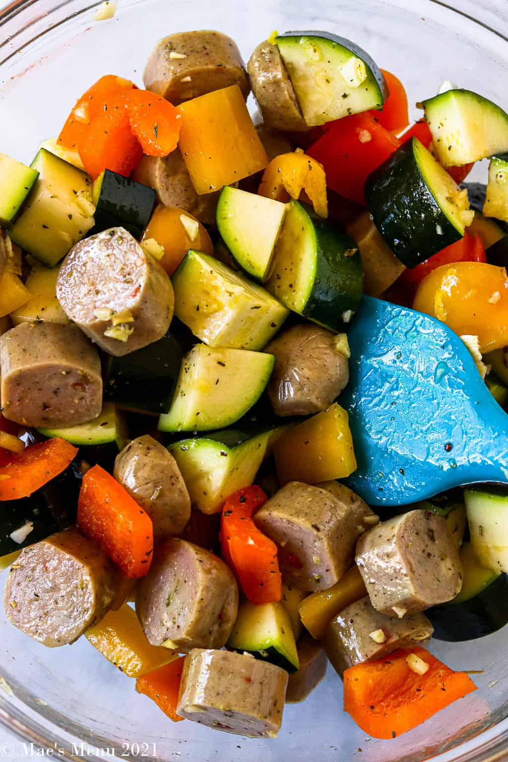 An overhead shot of a mixing bowl with vegetables, sausage, and seasonings