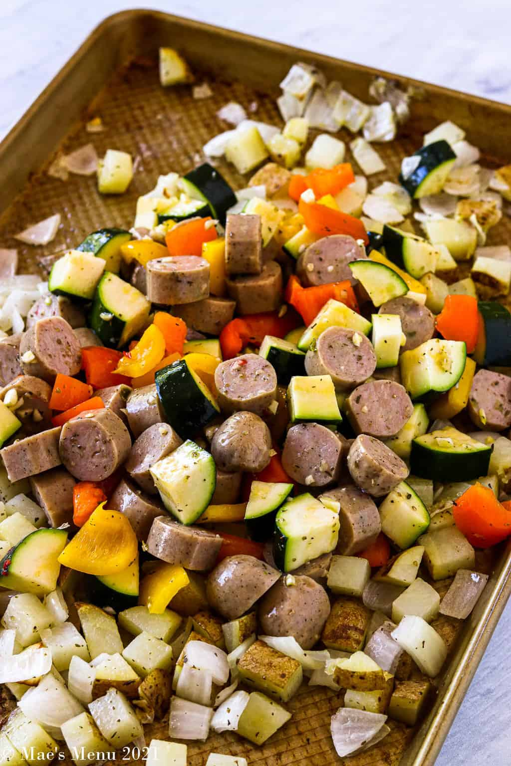 A side shot of a sheet pan full of potatoes, onions, veggies, and sausage with seasonings