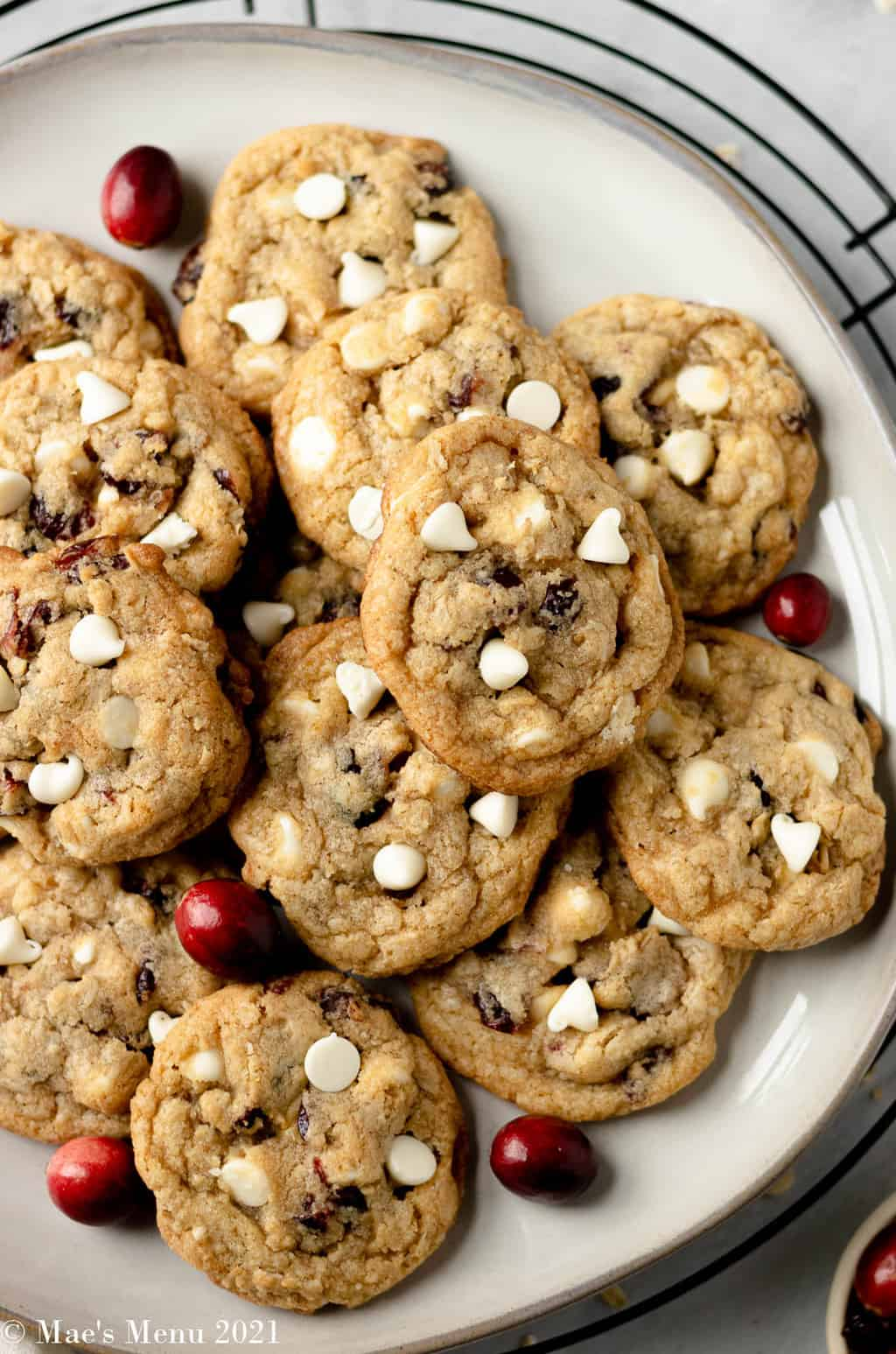 An up-close overhead shot of a white plate of white chocolate chip cookies with cranberries